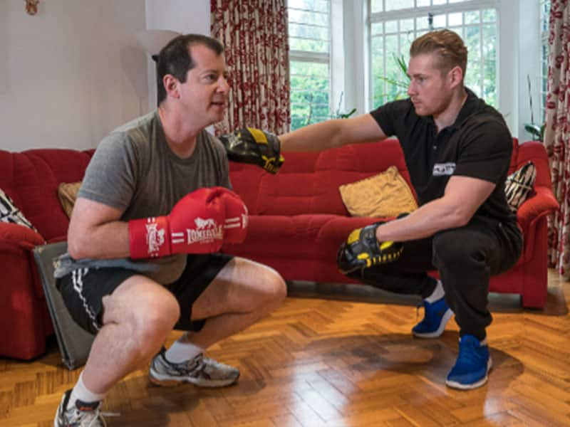 Mobile personal trainer training with a client at home