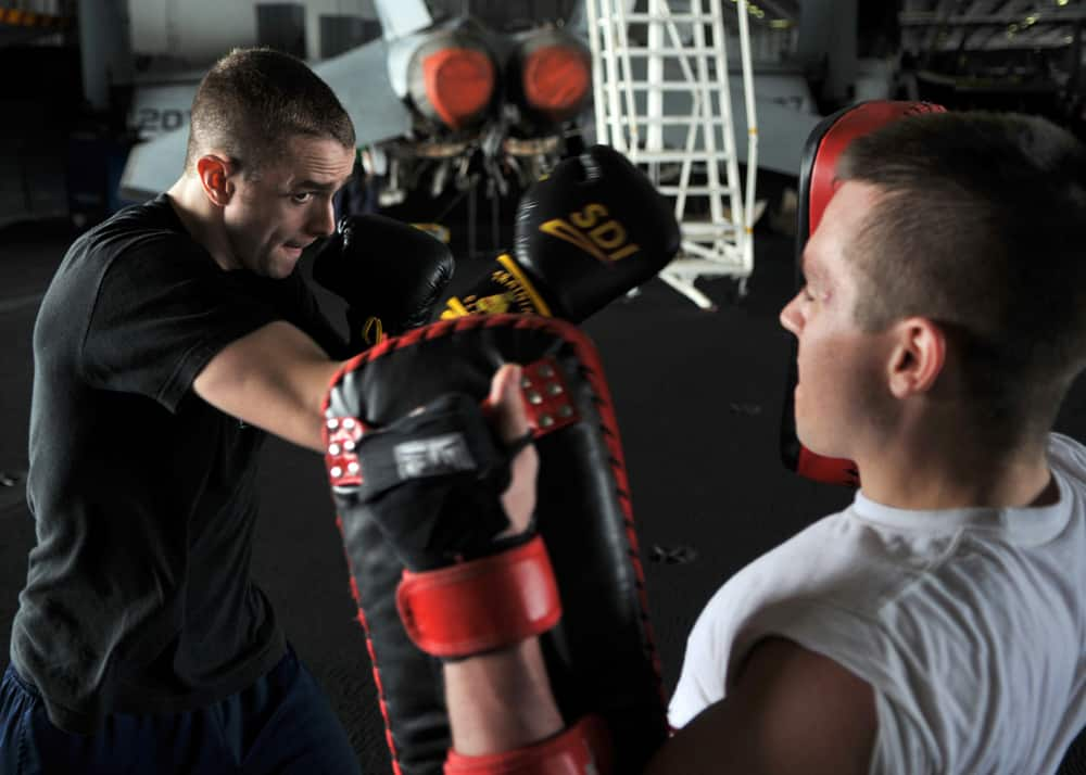 Mobile personal trainer boxing with client