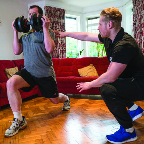 Client training with a mobile personal trainer at home.